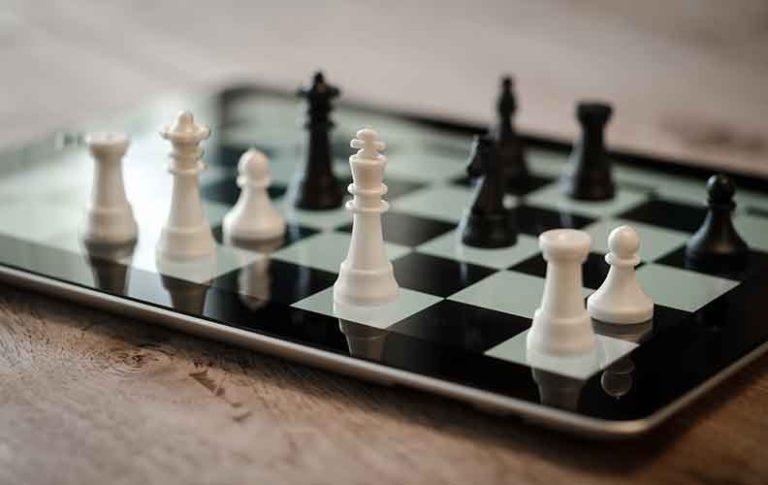 Figurice šaha na tabletu čija pozadina služi kao ploča za igru